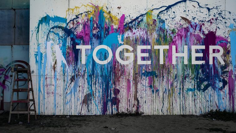 A large white canvas leaning against a wall made of grey bricks splashed with different colours of pain with the word Together across it in white letters.
