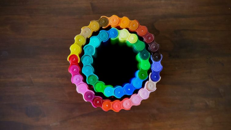 Different colour markers connected together in circles. The image is photographed from above so only the tops of the lids are visible. The table they're on is wood. It looks like two rainbow circles, one inside the other.