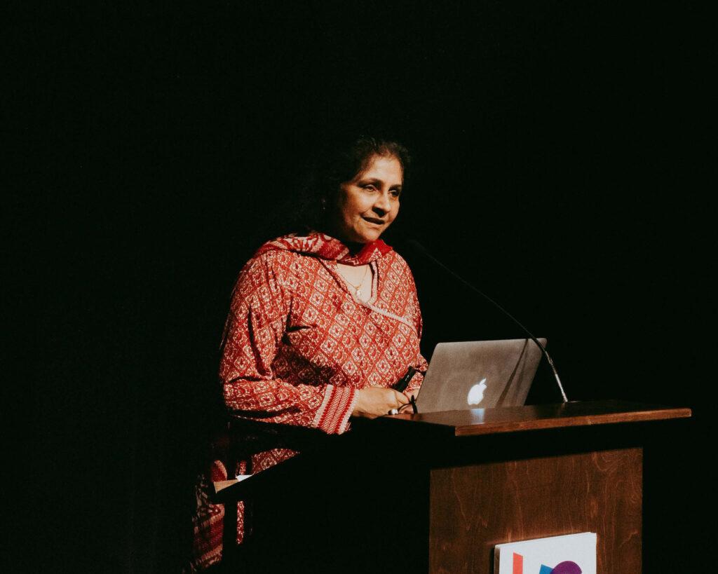 RDR executive director speaking at a podium in a dark auditorium
